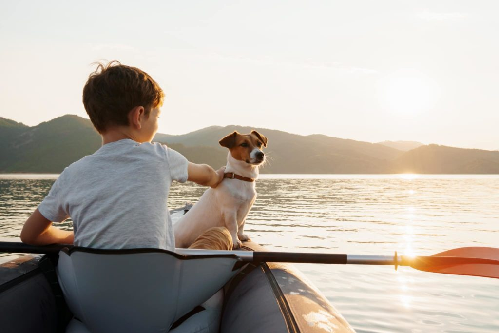 A small dog and boy in a boat while on summer vacation.