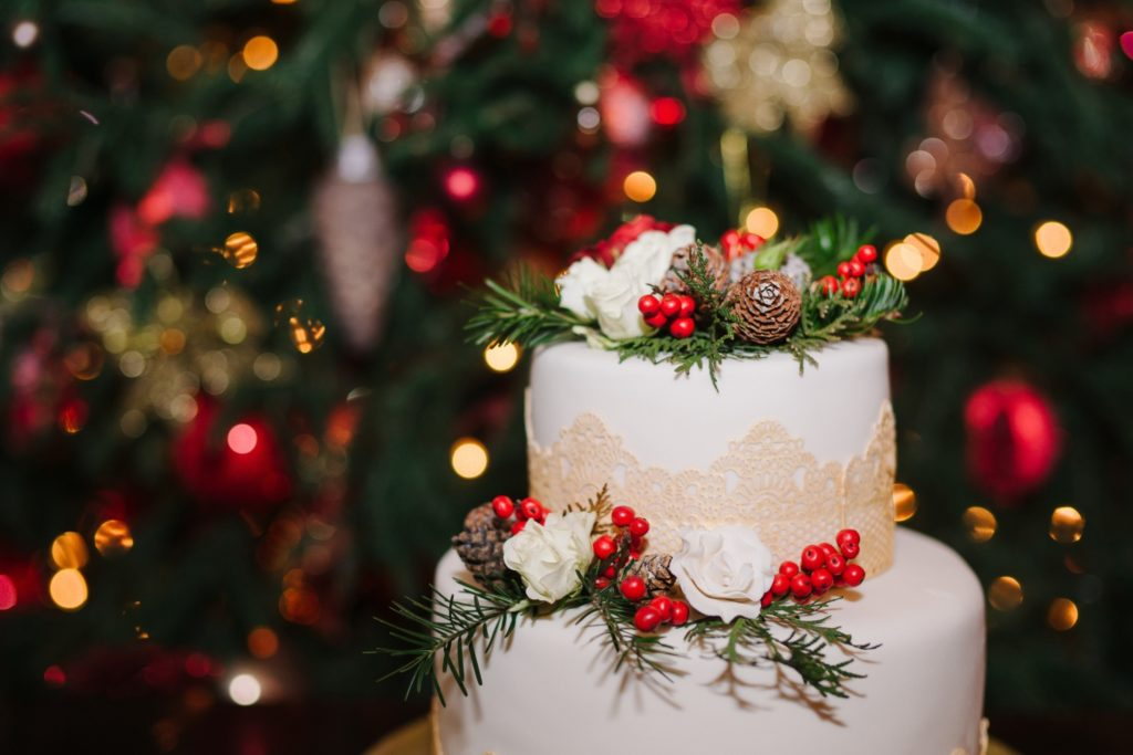 A wedding cake decorated with holiday decorations for a winter wedding.