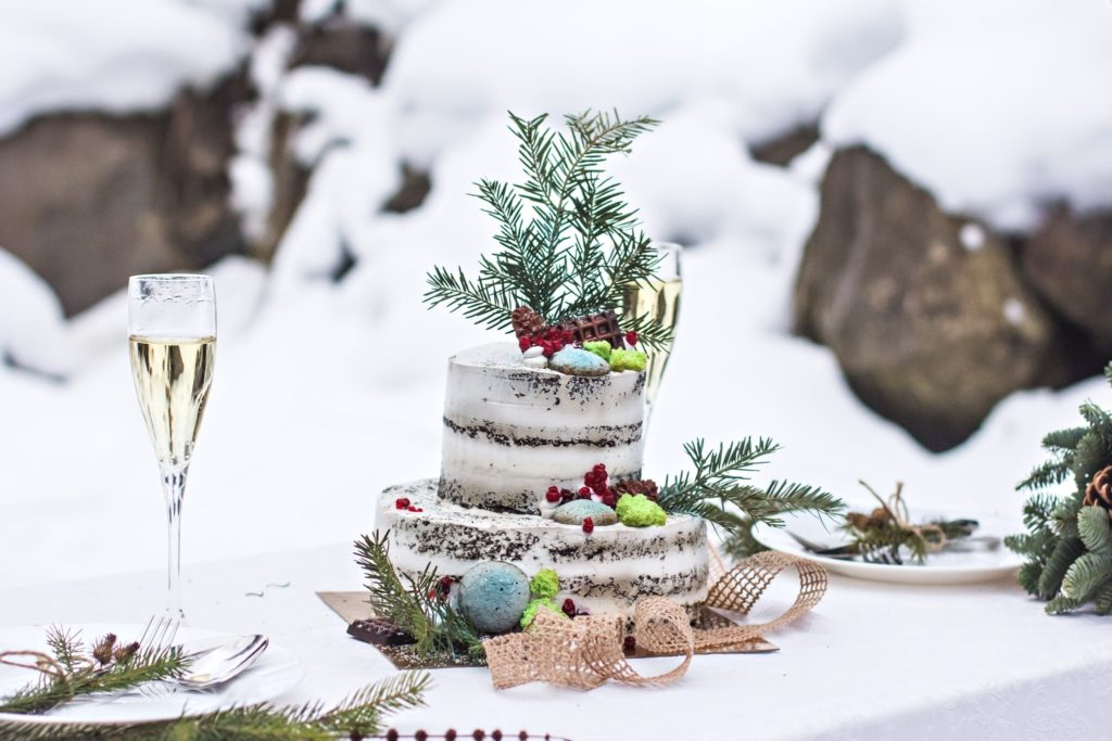 A winter wedding cake and place setting outside in the snow.