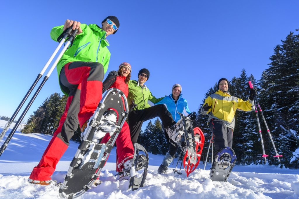 A family smiling and snowshoeing in Wisconsin in brightly colored winter attire.