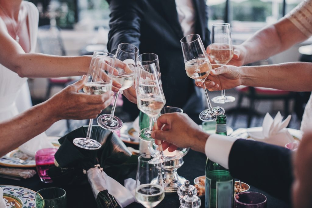 A wedding toasting at a party during a summer wedding.